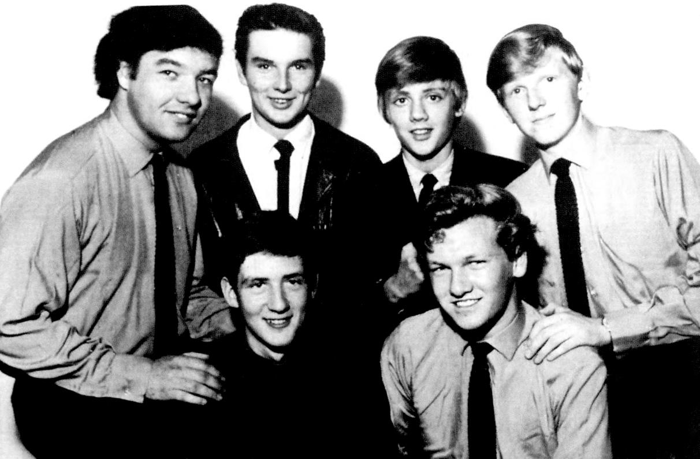 """Jedyne znane profesjonalne zdjęcie Johnny Quale and the Reaction, od lewej: John """"Acker"""" Snell (saksofon), Johnny """"Quale"""" Grose (wokal, górny rząd), Jim Craven (gitara basowa), Roger """"Splodge"""" Taylor (perkusja, górny rząd), Mike Dudley (gitara/organy) i Graham Hankins (gitara); 1965 r."""