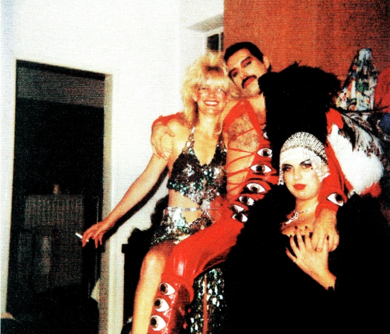 "A unique Polaroid photo of Freddie on the set of Queen's ""It's A Hard Life"" video, with his arm around the woman in his life at the time, Barbara Valentin"