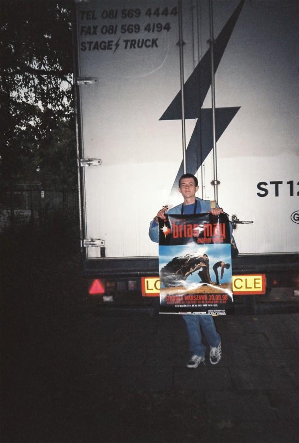 Autor na tle ciężarówki The Brian May Band, w rękach trzyma plakat promujący koncert; zdjęcie z prywatnych zbiorów Autora