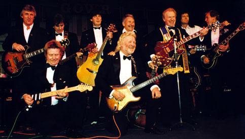 Bal Szczurów Wodnych, 29 listopada 1992 r.; od lewej: Bruce Welch, Joe Brown, George Harrison, Mike Read, Chas McDevitt, Lonnie Donegan, Bert Weedon (ówczesny Król Szczur), Brian May, Dec Cluskey; fot.: Doug McKenzie, gowr.net